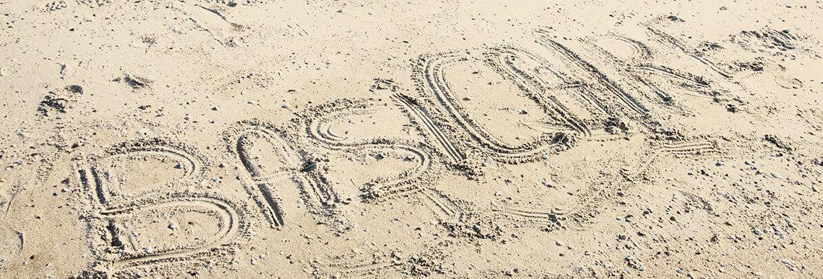 BasiCaire geschreven in het zand